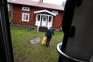 Ilva Andersson går hem med en kasse med böcker.