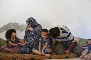 Ghofran 4 år, Oum Muhammed, Faysal 3 år, pappa Mahmoud och Omar 2 år sitter i det stora kombinerade sov och allrummet.