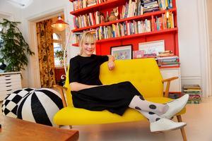 Den klarröda hyllväggen i vardagsrummet matchas med en gul soffa - Camilla gillar alla färger, men väljer med omsorg hur de kombineras.
