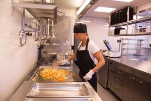 Tina Berg Dahlström vid stekbordet.. Tina, som gillar att laga mat, är tillfällig kock.
