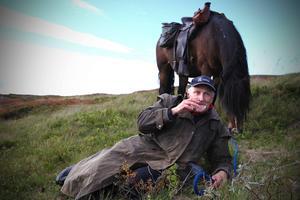Alf Kjellström äter en korvmacka och hästen får beta på lunchrasten.