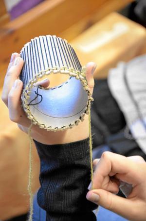 Väver väska. Här växer en väska till en mobiltelefon så sakteliga fram.