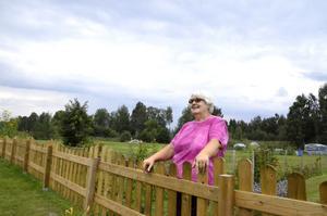 Berömmer feriepraktikanterna. Inga-Lisa Pettersson står framför det gräsområde som förut täcktes av högt gräs, men som nu har klippts ner av sommarjobbarna. Bild: Lars-Ivar Jansson