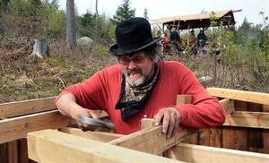 Lennart Larsson arbetar med att bygga en av lägrets förrådsbyggnader.