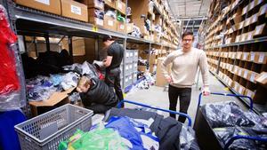 Alexander Blomqvist packar mer kläder att skänka. I bakgrunden gymcoach Måns Pettersson och Carl Broberg, produktspecialist.