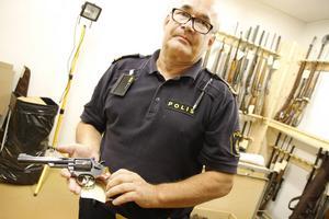 Polis Mats Holmberg visar omhändertagna vapen i polishuset i Hudiksvall.