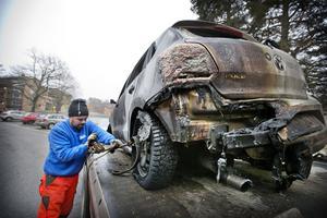 Pehr Albertsson från Ramströms bilbärgning  säkrar den brunna bilen på flaket för köra den vidare till skroten.