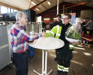 """Johan Lindgren och Alexander Jansson från Pirab Markservice vill lämna en blomma. """"Han har alltid svar på problemen,"""" säger de om Erik."""