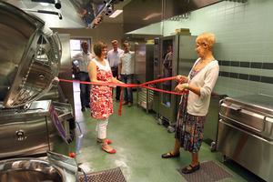 Helena Lundstedt som blir köksansvarig hjälper Birgitta Tapper (S), ordförande i kommunfullmäktige att dra i rosetten och förklara köket invigt.Omkring den 20 september räknas de första matportionerna att lagas.