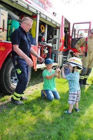 Ellion Andersson, 3, fick prova Kjell-Inge Wennbergs brandhjälm. Storebror Max Andersson, 11, passade på att föreviga stunden.
