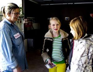 Marlene Lindgren Sköld, gruppledare på Värmestugan, tar emot pengarna av Vilma Jifjell och Ellen Sunnert.