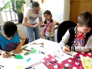 Skaparkraft. Baree visar bilder på mobilen och barnen målar fantasiträd.