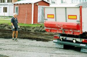 Just nu genomförs förberedande markarbeten utanför Myrvikens skola där multisportarenan ska ta ligga. Melcher Falkenberg, ordförande för den lokala skolstyrelsen, ser till att gruslasset hamnar där det ska.  Foto: Sandra Högman