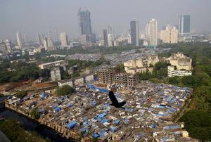 Slumområde granne med urbana livsmiljöer. Ojämlikheten i dagens Indien.