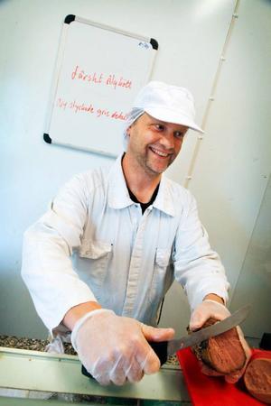 Ingvar Andersson snittar upp en skiva av specialiteten rökt nötkött. Och visst, vi köpte en bit för 82 kronor och 62 öre.