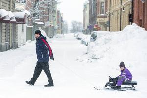 Emilia Thelin, fem år, tar sin snowracer ned till Stenstan med hjälp av pappa John.    – Jag tycker det är bra att det snöar för då kan jag åka slalom, säger hon.