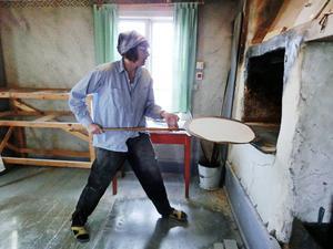 Ruttan Speijer laddar in tunnbrödsdegen i ugnen. Bakstugan har Åreskutan som inramning i fönstret bakom henne.