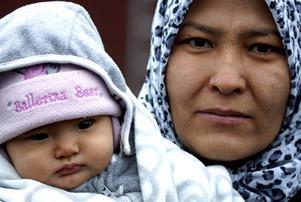 Mor och dotter i det tillfälliga flyktinglägret på Åstön. Modern har kommit hit hela den långa vägen från Afghanistan. Dottern har färdats lite kortare. Hon är född under flykten från våld och terror. Det novembergråa mörkret i novembergråa mörkret i flyktinglägret speglas i ögonen. Oro, smärta och ovisshet också. Ännu en sysslolös dag i väntan på ett besked som kommer att dröja och som dom kanske inte vill ha när det väl kommer. Vinka och le mot flyktingarna när du passerar flyktingboendet.