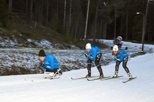 Här ses Aron på träning i sit-ski med sina coacher Emil Jönsson och Anna Haag.