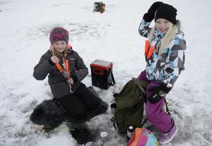 Maija Magnusson och Agnes Adolfsson har roligt tillsammans när de försöker locka fiskarna upp på land.