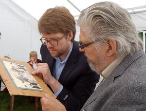 Jan Östensson, till höger, och Pontus Gärdshag letar efter en signatur på en Jenny Nyström-teckning.
