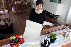 Elin Westlund visar här den damastväv med mönster utifrån en bård hon hittade i hälsingegård Löka strax utanför Alfta.