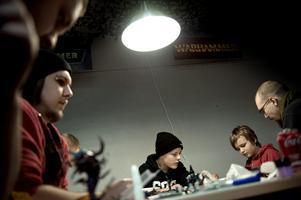 Samling. Sebastian Eriksson, Simon och Erik Grundelius och Peter Hakulinen målar figurer till strategispel på brädspelskafét Bunkern.