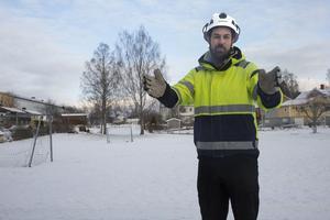 Här mitt för den lilla fotbollsplanen kommer tunneln för gående och cyklister att byggas, berättar Kristoffer Sjöstrand vid Skanska. Tunneln byggs i förväg och sätts på plats i augusti.
