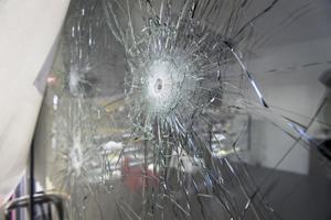 Skotthål i ett fönster i det kafé i förorten Rinkeby i nordvästra Stockholm där två personer sköts till döds i december.