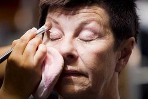 STEG 3 – SMINKET. Lena Coskun börjar med att lägga en lätt grund och fyller i Ulla Perssons ögonbryn.