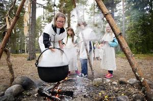 Igår var Norrflärkeskolan i Gene fornby. De äldre barnen fick prova på att vara arkeologer, medan de yngre fick leva järnåldersliv. Här hjälper läraren Katarina Strömberg Nathalie Englund, Ella Nilsson och Jonna Byström att tillaga kams i grytan över elden.