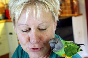 Papegojan Fanny sitter nöjt på Carins axel.