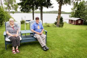 Gun och Ivan Larsson var på bild i tidningen för femton år sedan. Den såg ut ungefär precis så här: samma soffa, samma sjö, samma båtar i bakgrunden. Det enda som saknas är deras fantastiska tax Baltazar.