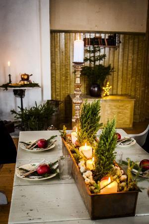 Bordet är dukat för julfest med grankvistar, röda äpplen och en trälåda som fyllts med mossa och ljus.