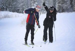 Emil Svensson, hjälper Markus Arvidsson, med att lossa skorna från skidorna efter premiärturen vid Åsarna gamla kyrka.