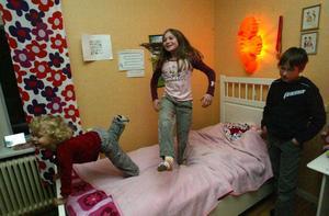 Linnea och Sandra hoppar i sängen medan Marcus lugnt ser på. Bus finns det fortfarande plats för i familjen, men bråken har blivit betydligt färre. På väggen syns