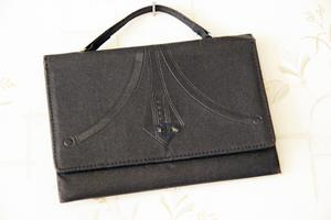 En svart handväska med jugendmönster.