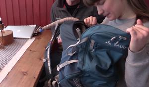 Sara visar ryggsäcken där de ska ha med lite extra kläder, mat och dryck i den egendesignade