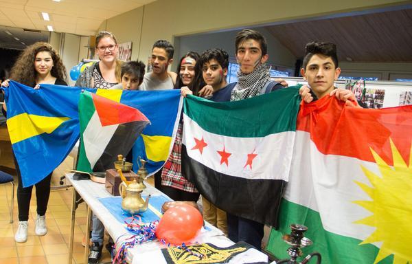 Läraren Jenny Eldstål och några elever håller upp Sveriges, Palestinas, Syriens och Kurdistans flagga tillsammans.