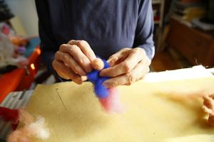 Efter att underkjolen fästs gör Karin ett hål i överklänningen och trär på den liksom på en docka...
