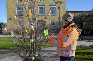 Påskris. Karin Andersson på parkavdelningen på kommunen dekorerar påskris framför Kumla stadshus.