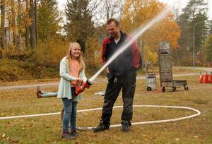 Wilma Halvarsson, 9, fick under pappa Peters översyn testa att spruta vatten. Peter Halvarsson vet i nuläget inget om kårens framtid i byn.