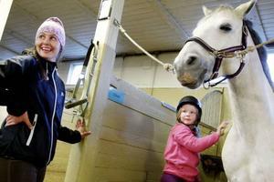 Erika Mårdberg finns på plats som fritidsledare för barn som hänger i stallet på Östersund Frösö ridskola. Elina Hamberg Högström har just fått en lektion i ryktning. Och hästen Lanzelot ser nöjd ut.