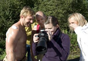 Brandmännen Emil Grip och Mattias Lundberg granskar nöjt resultatet av fotomodellandet. Fotografen Emmelie Åslin ställer upp ideellt. Till höger syns Märtha Strandlund som var med och startade Laris änglar.