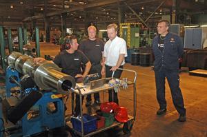 ULTRALJUD. Johan Mårtensson lyssnar med ultraljud efter sprickor i en koppling. Produktionschef Fredrik Stolpe, vd Per Jarbelius och Tore Almgren, ordförande i Metallklubben på företaget, betraktar jobbet.