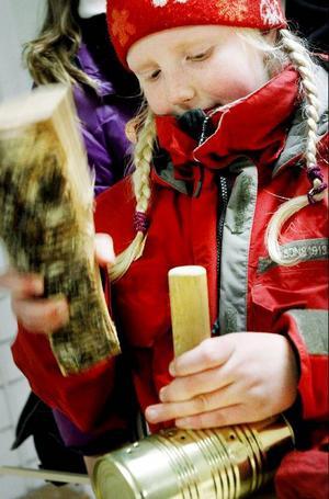 Anni Blomqvist får till några hål med hjälp av en spik som är fäst i ett stycke trä. Hon använder en träbit att slå med.Det ska bli en lykta.