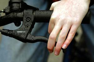 En hand bromsar en cykel med hjälp av en handbroms.
