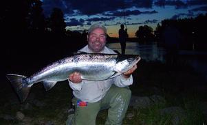 SOMMARNATTENS LEENDE. Kalle Sundblad, Uppsala visar glatt upp sin lax på 14,5 kilo som han tog vid Fasta fisket på tisdagskvällen