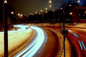 Spåren efter bilarnas ljus tagna med lång exponeringstid ger en effektfull, fartfylld bild. Av en slump kom en polisbil i full fart på utryckning med blåljusen påslagna, vilket gav dessa blåa