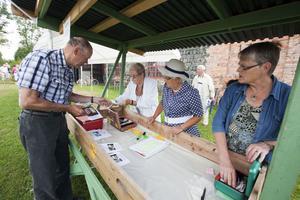 Besökaren Ivar Persson kvitterar ut sin biljett från funktionärerna Ingrid Elevall, Ingrid Björk och Alice Lindgren. Biljettförsäljningen har inte gått lika bra i år som förra året i Gammelstilla.